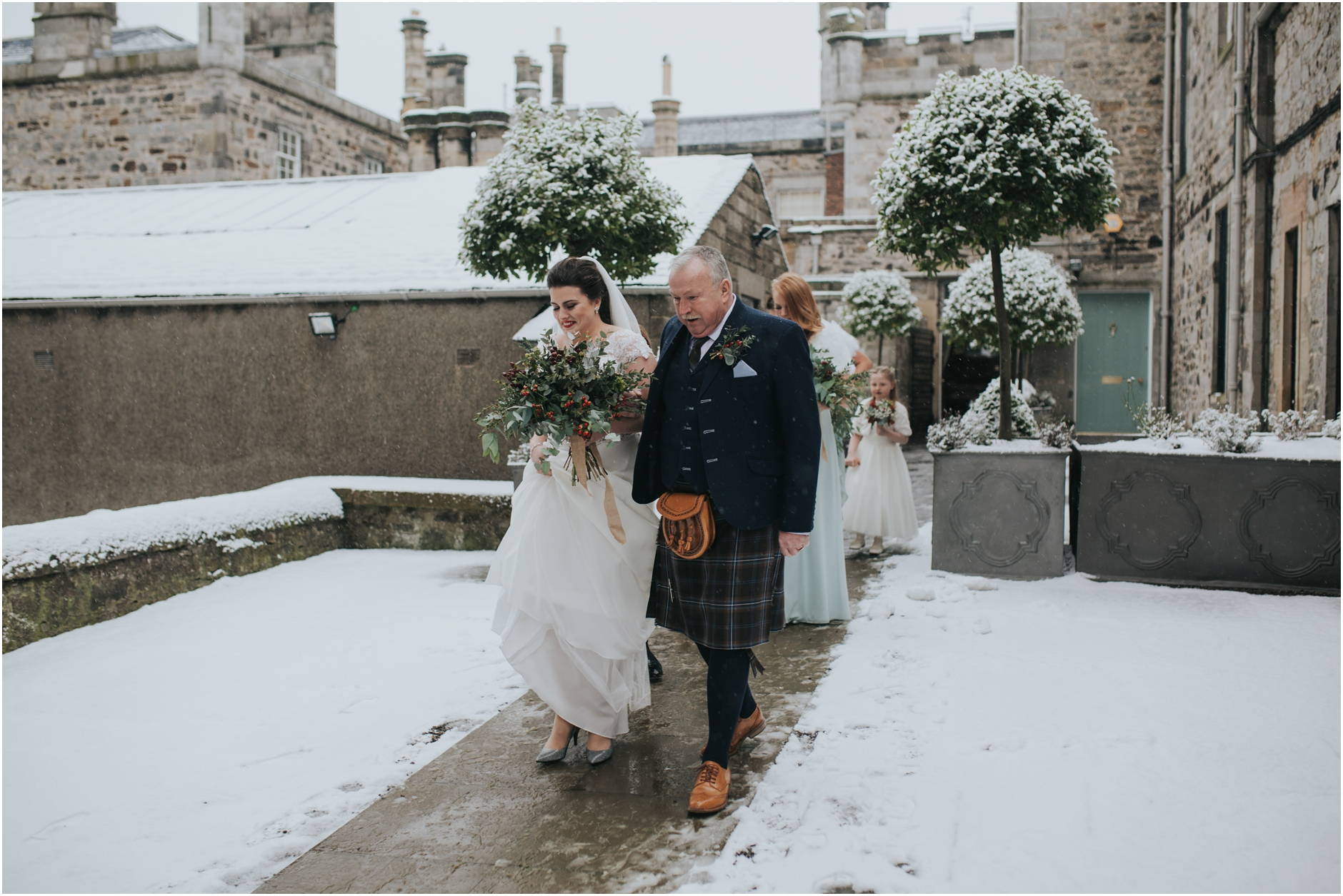 dundas castle edinburgh wedding winter snowy bride and her dad walking across the snow before the ceremony