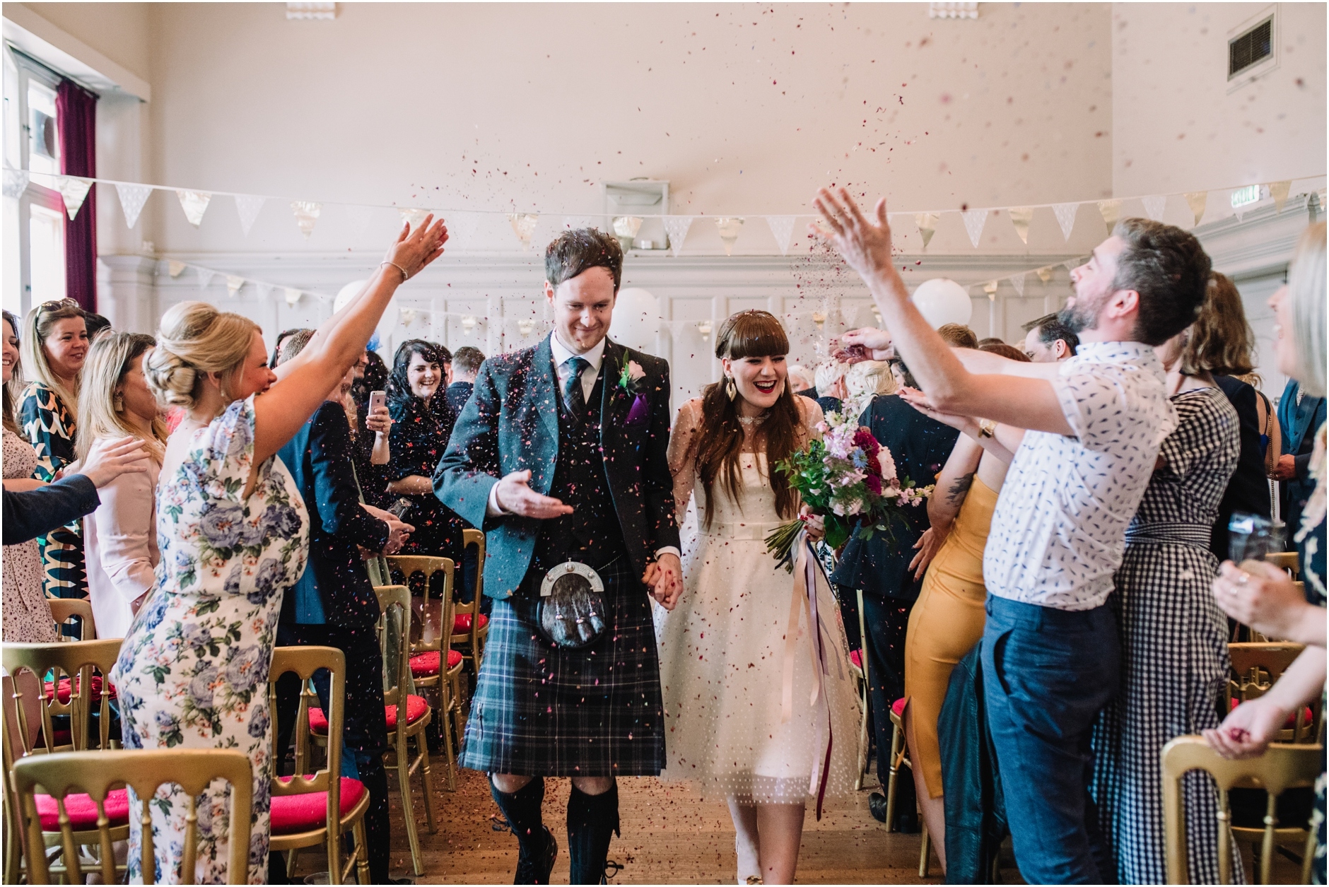 summerhall wedding edinburgh, couple getting confetti thrown as they walk up the isle
