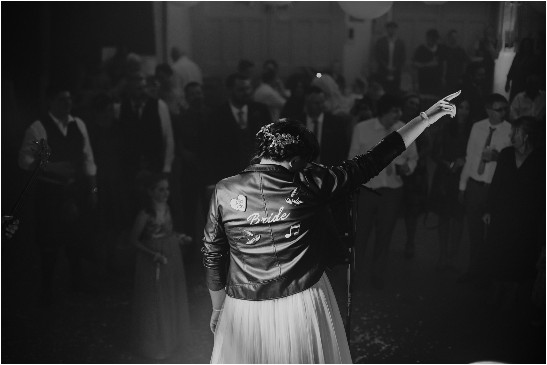 rock n roll birde on her wedding day playing with her band wearing a leather jacket over her wedding dress