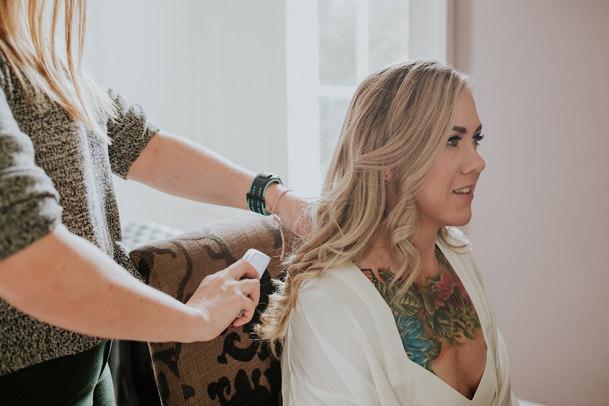 bride having her hair styled on her wedding day