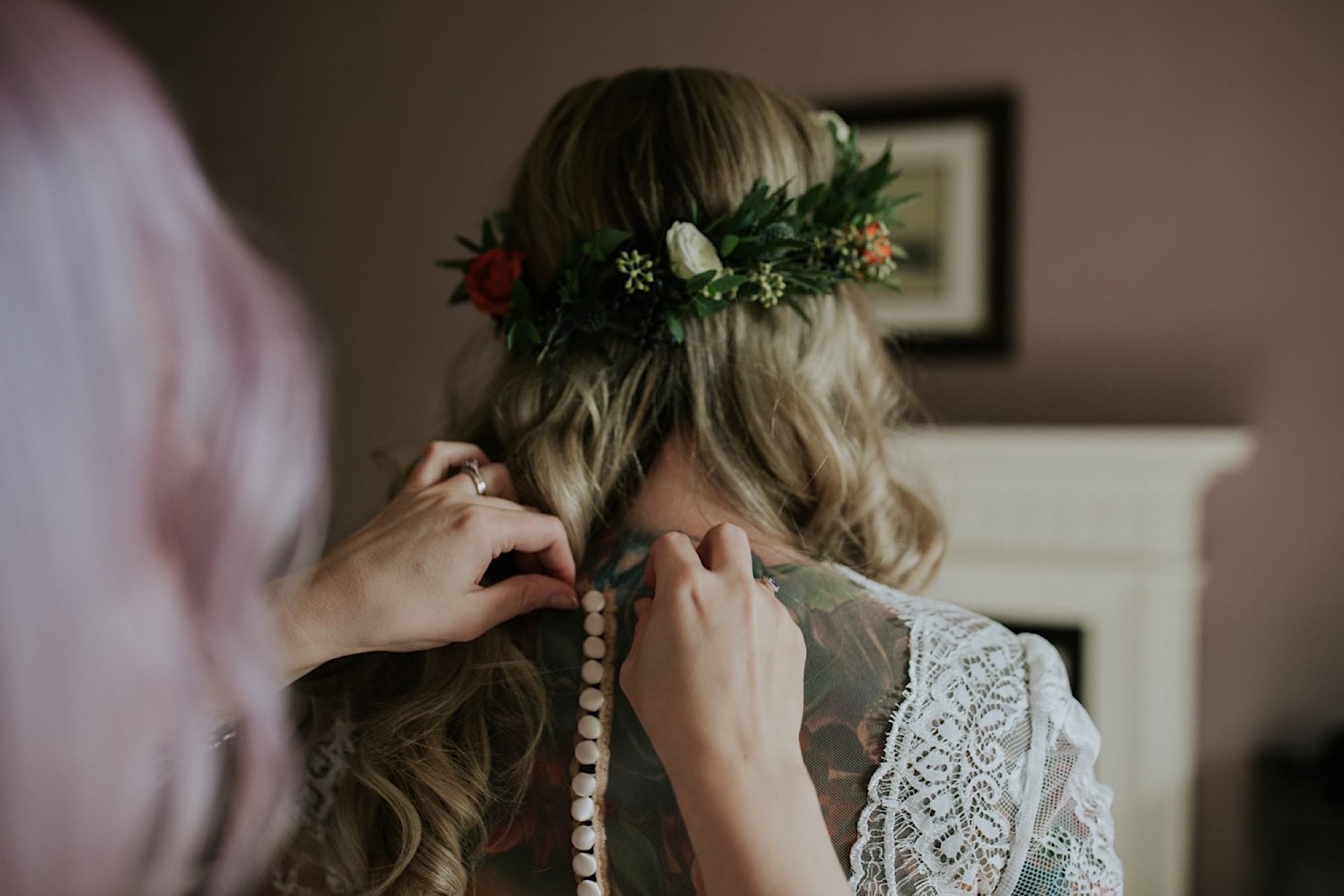 bride having her dress done up