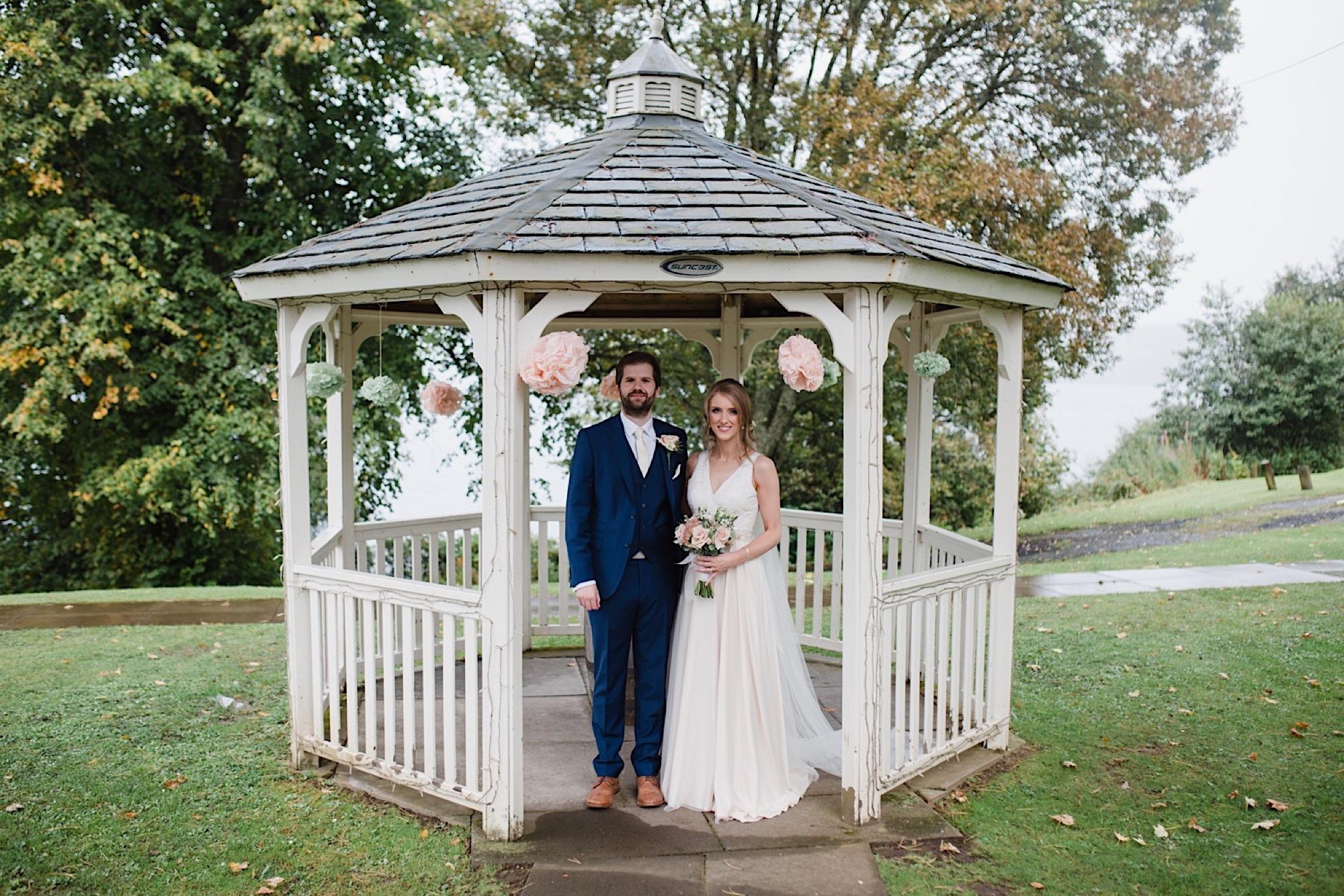 birde and groom rainy wedding day under pergola