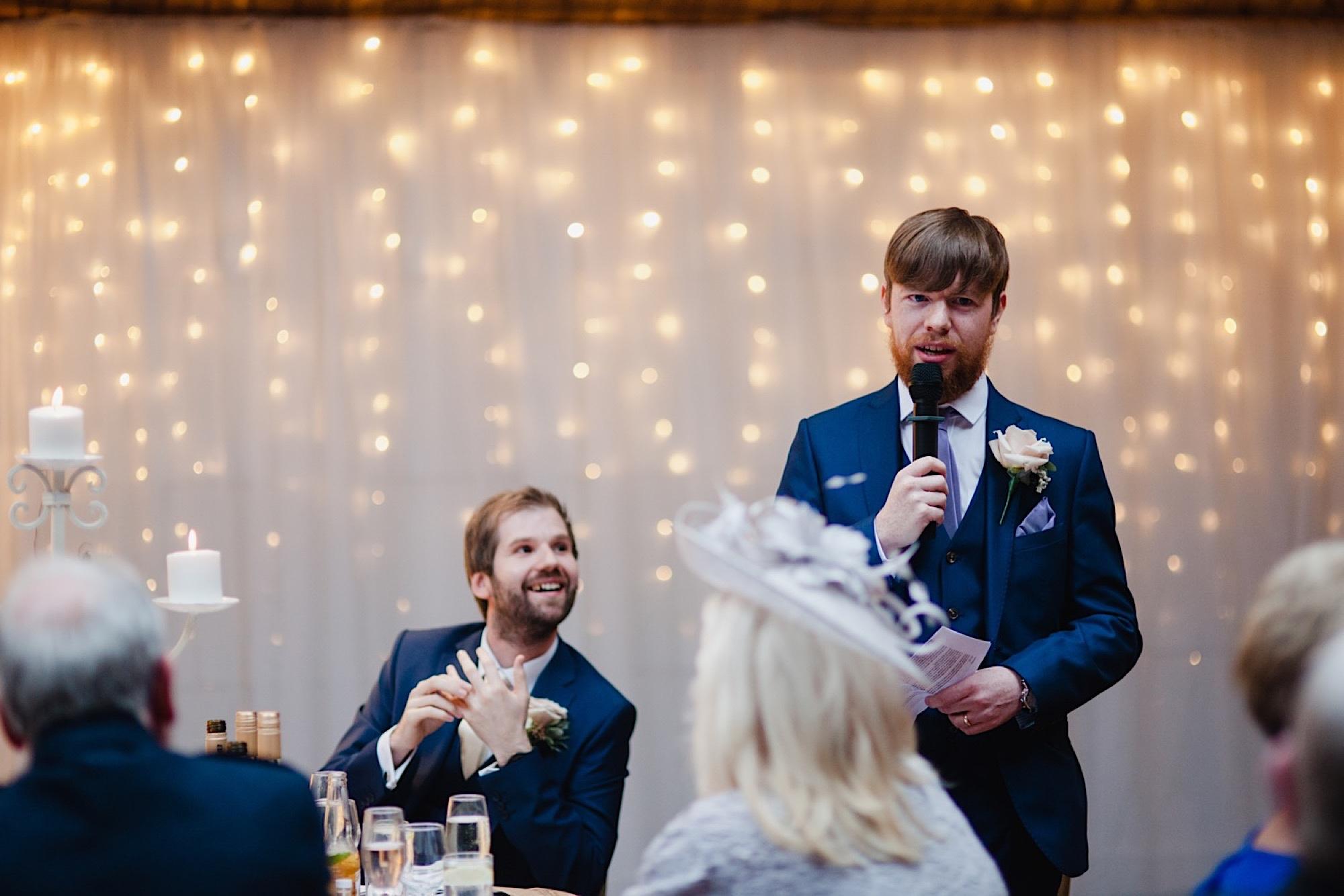 best man wedding speech infront of a fairy light curtain