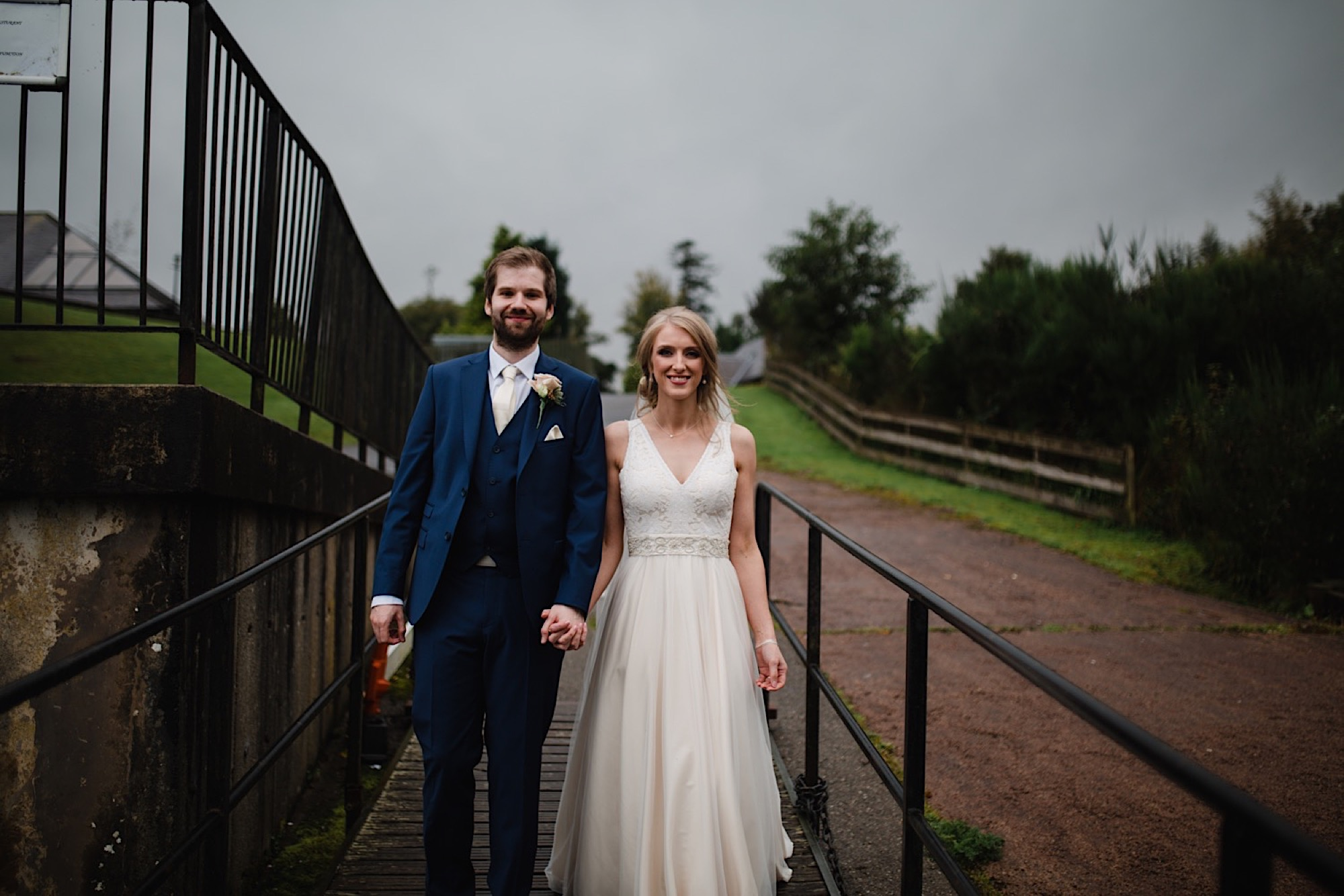 bride and groom on the banks of loch lomand with a dark and moody sky as the rain stops