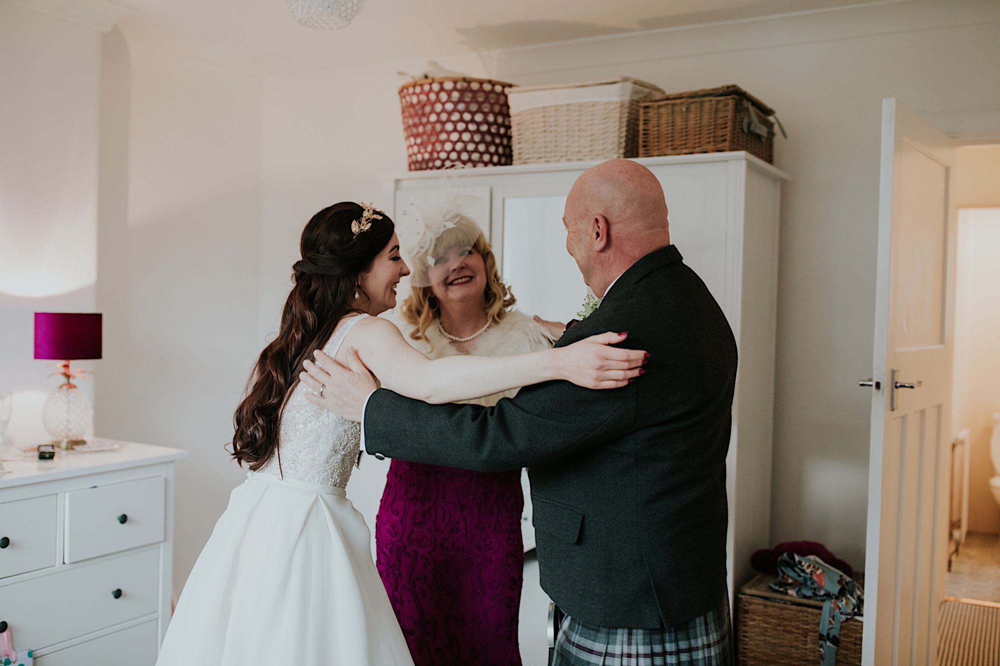 bride hugger her mum and dad on the wedding morning