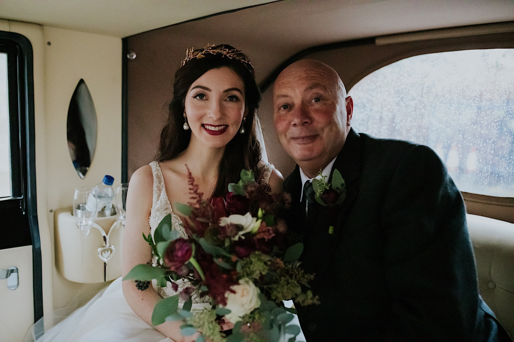 bride and her dad smiling in the back of the wedding car
