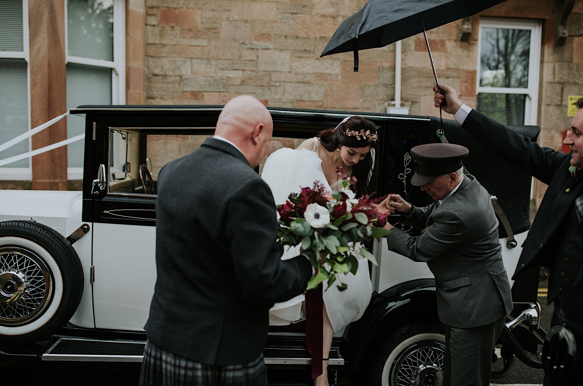 bride getting out of the wedding car in the rain