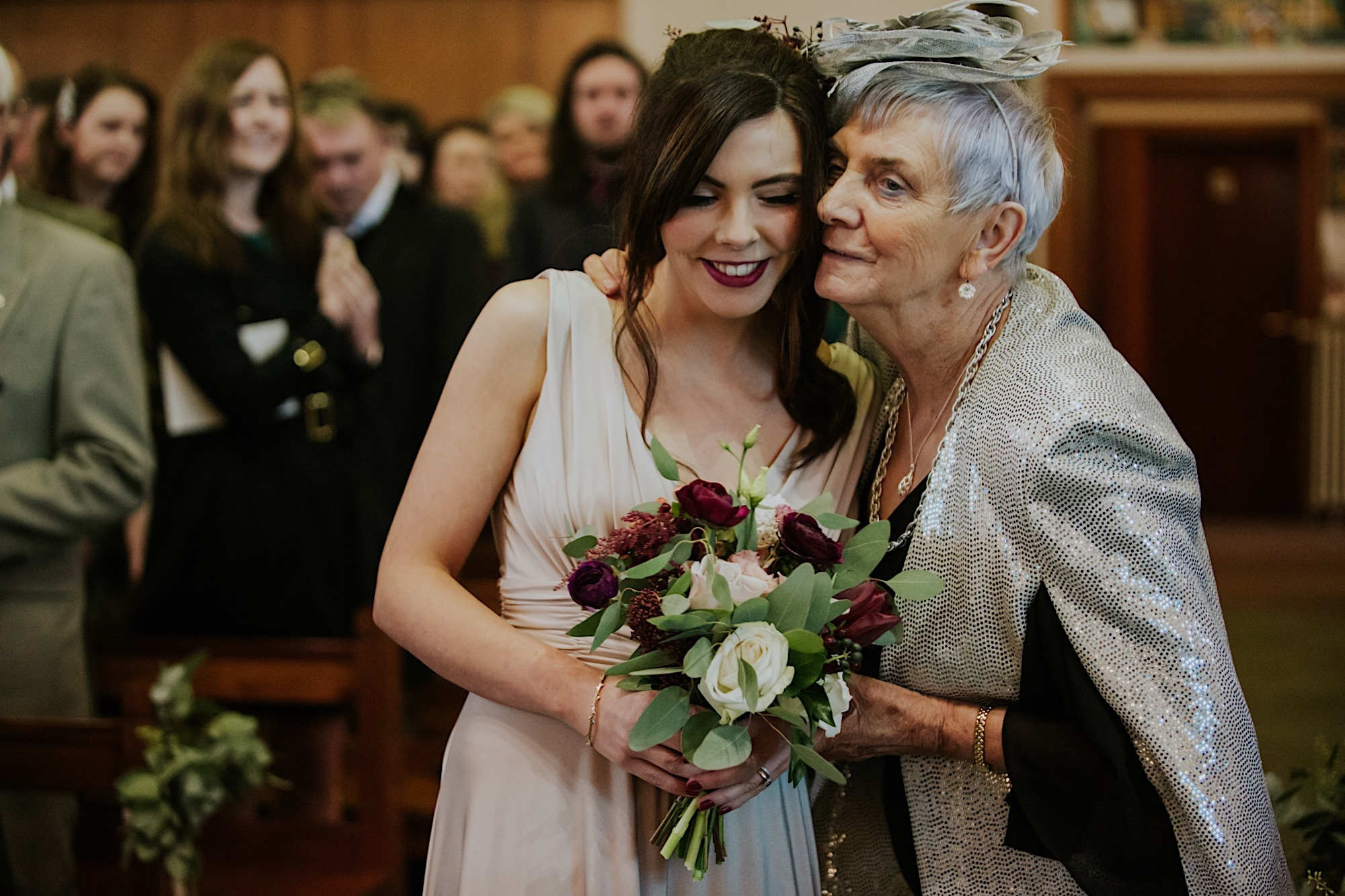 bridsmaid greeting her grandmother as she walks down the isle