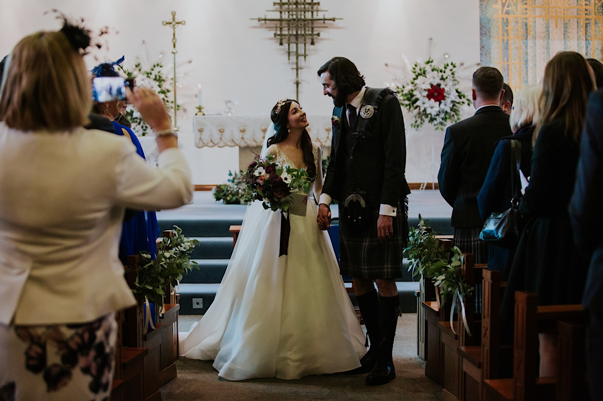 bride and groom walking out of ceremony looking at each other with smiles